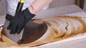 Закалять расплавленный шоколад на естественном камне Руки женщины и конец-вверх шпателя сток-видео