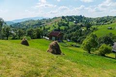 Закарпатская деревня при сенаж построенный в хате журнала около разбросанных холмов домов Стоковые Изображения RF