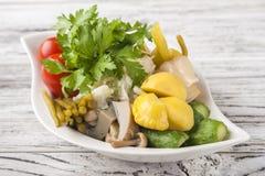Заквашенная еда в плите на белом текстурном деревянном столе Огурцы, цукини, чеснок, маринад, томаты, капуста, ramson, равенства стоковая фотография rf