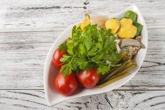 Заквашенная еда в плите на белом текстурном деревянном столе Огурцы, цукини, чеснок, маринад, томаты, капуста, ramson, равенства стоковые фото