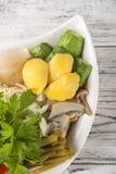 Заквашенная еда в плите на белом текстурном деревянном столе Огурцы, цукини, чеснок, маринад, томаты, капуста, ramson, равенства стоковые изображения