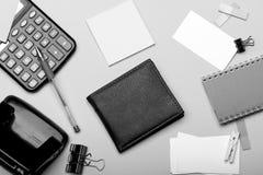 Закладки, серая тетрадь, дырокол, зажимка для белья и ручка на cyan голубой предпосылке Канцелярские принадлежности, бумажник и к стоковая фотография
