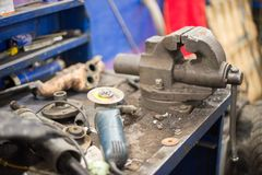 заклепка орудийного металла аппликатора заклепывает мастерскую Тиски и верстачный шлифовальный станок на металлическом верстаке с стоковое изображение rf