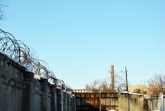 Заключите загородку в тюрьму колючей проволоки, ландшафт зимы солнечный с высокой трубой, голубым небом стоковые изображения