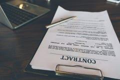 Заключите контракт бумаги и ручку с компьтер-книжкой на деревянном столе, законном contr стоковая фотография