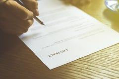 Заключите контракт документ, бумагу знака 2 людей в офисе тонизированное увяданное изображение стоковые изображения