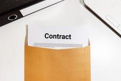 Заключите контракт документ в конверте с файлом и тетрадью на столе - b стоковая фотография rf
