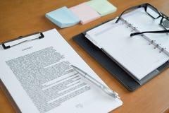 заключите контракт документ, тетрадь & ручку на деревянном столе стоковое изображение