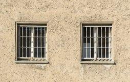 Заключите стену в тюрьму с 2 окнами с решеткой тюрьмы Стоковое фото RF