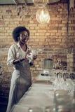 Заколдовывая испуская лучи Афроамериканец жизнерадостно светя стеклам на баре просторной квартиры стоковые изображения