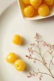Законсервированные желтые вишни на плите и хворостине с малыми цветками Стоковое Фото