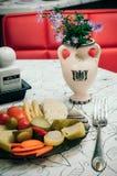 Законсервированные овощи на темной прозрачной плите рядом с вазой  Стоковая Фотография