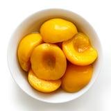 Законсервированные половины персика в шаре изолированном на белой предпосылке От a стоковое изображение rf
