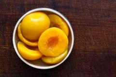 Законсервированные половины персика в шаре изолированном на темной предпосылке От ab стоковая фотография