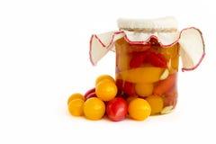 Законсервированные томаты в опарнике и свежие изолированные томаты Стоковые Изображения