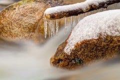 Закоптелая холодная вода потока горы в зимнем времени Длинные кристаллические сосульки висят над milky уровнем воды стоковые изображения rf