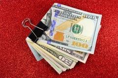 Закрепленные деньги на красной sparkly предпосылке Стоковое фото RF