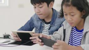 Закройте вверх азиатской милой девушки и молодого мальчика играя в конкурсной видеоигре на смартфонах видеоматериал
