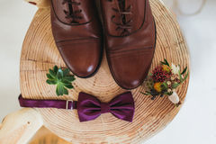 Закройте вверх аксессуаров современного человека boutonniere фиолетовой бабочки, кожаных ботинок, пояса и цветка на деревянном ст Стоковая Фотография RF