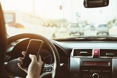 Закройте вверх дамы управляя автомобилем опасно пока использующ мобильный телефон Стоковые Изображения