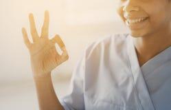 Закройте вверх африканских сотрудник военно-медицинской службы или медсестры показывая одобренный знак Стоковые Фото