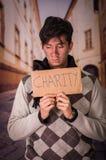 Закройте вверх бездомные как с описанием картона призрения, в запачканной предпосылке Стоковые Фотографии RF