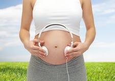 Закройте вверх беременной женщины и наушников на tummy Стоковое Изображение