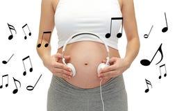 Закройте вверх беременной женщины и наушников на tummy Стоковое Изображение RF