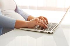 Закройте вверх беременной женщины работая на компьтер-книжке Стоковая Фотография
