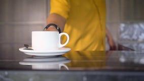 Закройте вверх белой кофейной чашки помещенной на таблице кельнером в желтой рубашке видеоматериал