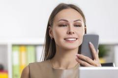 Закройте вверх белокурой женщины смотря телефон Стоковое Фото