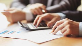Закройте вверх бизнесмена или рука бухгалтера держа карандаш работая на калькуляторе для того чтобы высчитать финансовые данные с стоковое изображение rf