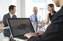 Закройте вверх бизнесмена используя компьтер-книжку во время собрания членов управления вокруг Стоковое Фото