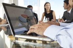 Закройте вверх бизнесмена используя компьтер-книжку во время собрания членов управления вокруг Стоковое Изображение RF