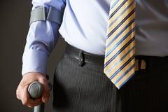 Закройте вверх бизнесмена используя костыль Стоковое Фото