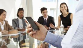 Закройте вверх бизнесмена используя мобильный телефон во время собрания членов управления вокруг стеклянного стола Стоковые Изображения