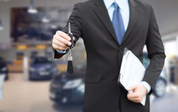 Закройте вверх бизнесмена или продавца давая ключ автомобиля Стоковые Изображения RF