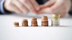 Закройте вверх бизнесмена кладя монетки в столбцы сток-видео