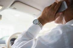 Закройте вверх бизнесмена на телефоне в его автомобиле Стоковые Фото