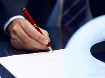 Закройте вверх бизнесмена подписывая подряд. Стоковое фото RF