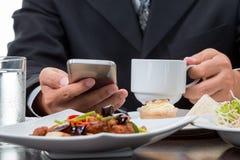 Закройте вверх бизнесмена проверяя новости от мобильного телефона пока ел завтрак Стоковые Изображения