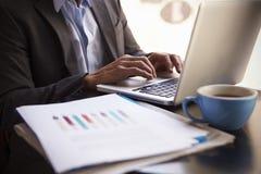 Закройте вверх бизнесмена работая на компьтер-книжке окном офиса Стоковое Изображение RF
