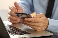 закройте вверх бизнесмена работая с com мобильного телефона и компьтер-книжки Стоковое Изображение