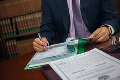 Закройте вверх бизнесмена юриста сидя на таблице и подписывая документе Стоковое Изображение
