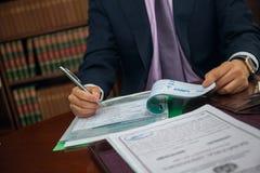 Закройте вверх бизнесмена юриста сидя на таблице и подписывая документе Стоковые Изображения RF