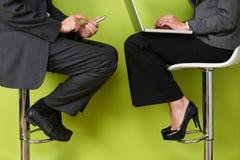 Закройте вверх бизнесменов используя компьтер-книжку и мобильный телефон Стоковое фото RF