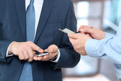 Закройте вверх бизнесменов используя передвижные умные телефоны стоковые изображения