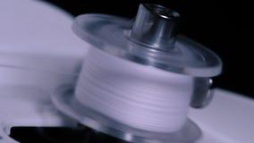 Закройте вверх большой катышкы с тонким белым потоком на работе профессиональной швейной машины Съемка шить катушкы быть обветрен сток-видео