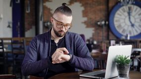 Закройте вверх бородатого битника сидя в ресторане, смотреть и касающем smartwatch Мужской дизайнер ждет клиента сток-видео