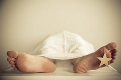 Закройте вверх босых ног при прикрепленная звезда золота Стоковое Изображение